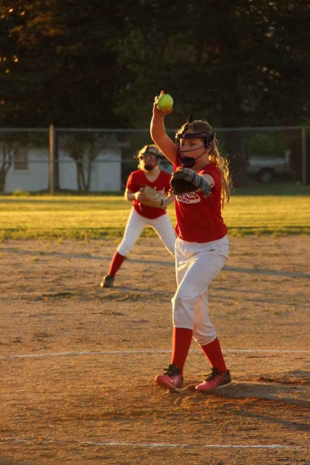 girl wearing baseball mitts holding soft ball