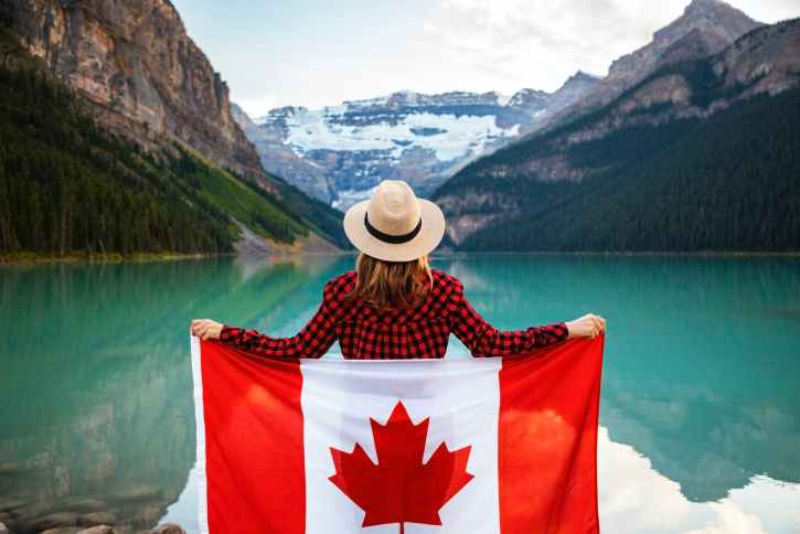 woman wearing red and black checkered dress shirt and beige fedora hat holding canada flag looking at lake