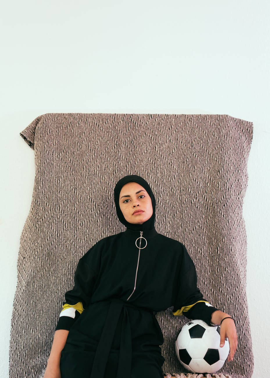 photo of woman in black hijab holding soccer ball