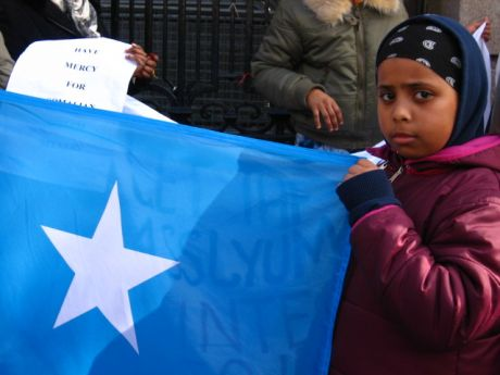 young girl in pink jacket holds up somali flag outside dail in dublin city