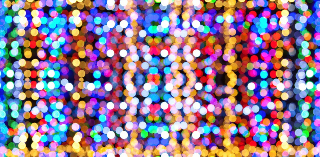 Neon blue, red, yellow, dark blue, orange, green white polkadotted blurs on a background