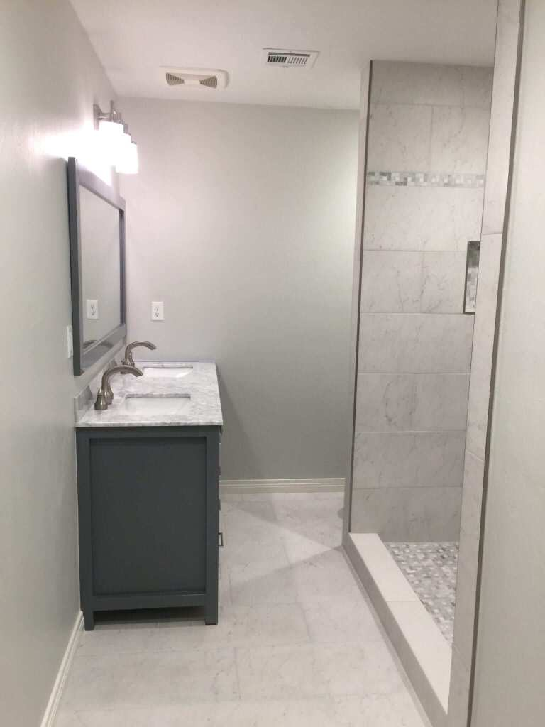 Bathroom remodeled with new tile floors, shower tile, glass shower door, counters, vanity, mirror, toilet, and lighting.