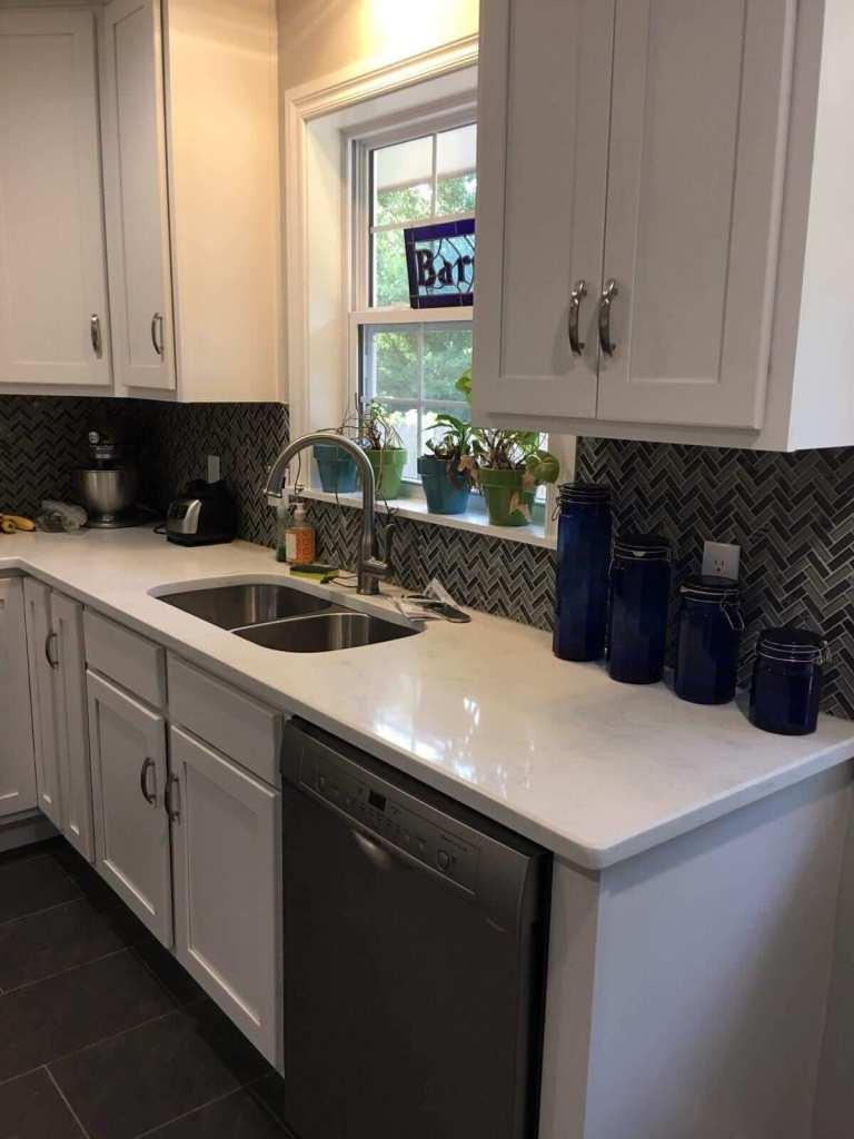 Kitchen remodeled with new floor tile, backsplash tile, vent hood, cabinets, paint, floor tile, and appliances.