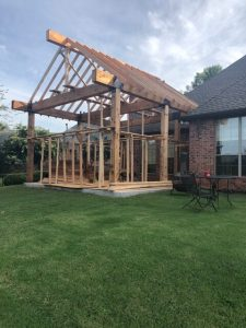 Photo of framing for covered patio with cedar columns and beams.