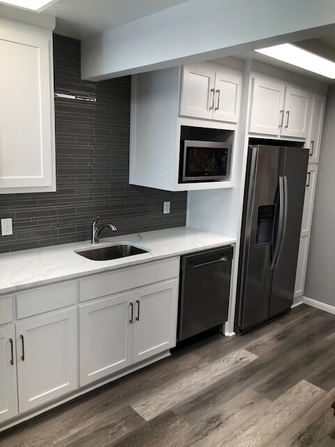 A commercial break room with a new backsplash, quartz counters, cabinets, engineered wood flooring, and appliances.