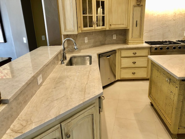 "Kitchen with new quartzite countertops and porcelain 24"" x 24"" floors."