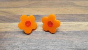 orange daisy studs with live red centres