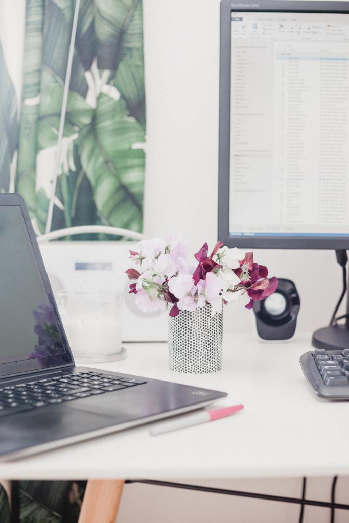 photo of laptop on a table, next to a vase of flowers