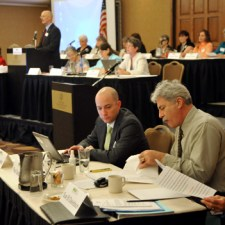 Photo of event delegates at a conference. One man is standing and addressing the group from a stage, while a small group of men reviews paperwork in the foreground.