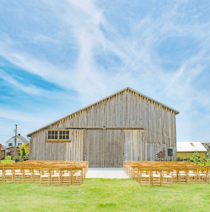 barn with chairs in front, set up for a wedding