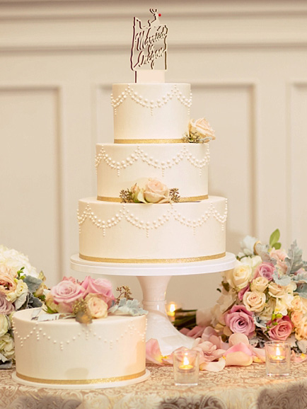 three tier wedding cake on table, surrounded by flowers