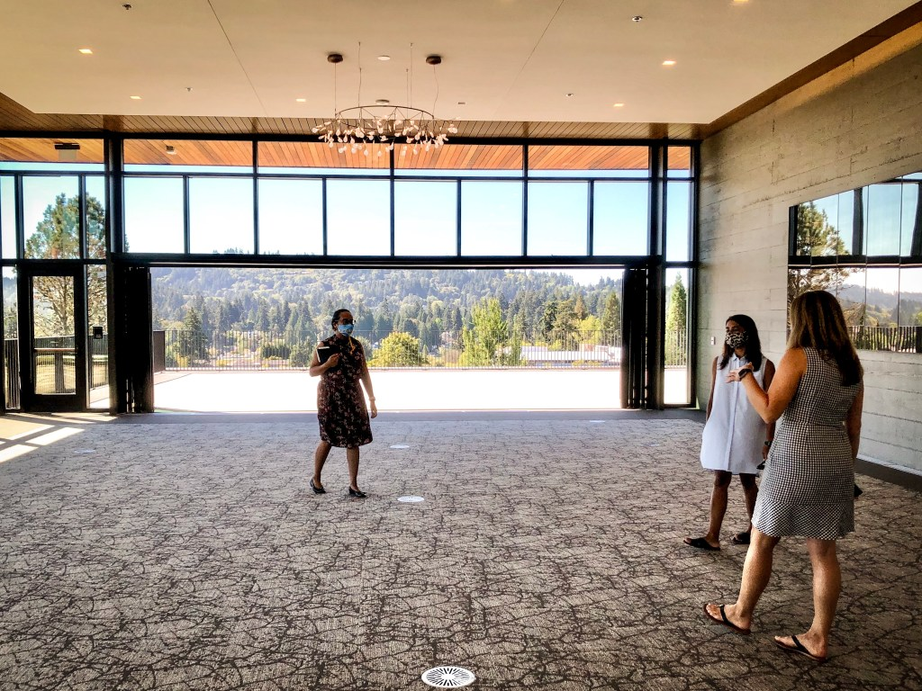 Portland event planning photo of 3 women standing in a ballroom under a chandelier. A view of Lake Oswego Oregon is behind them.