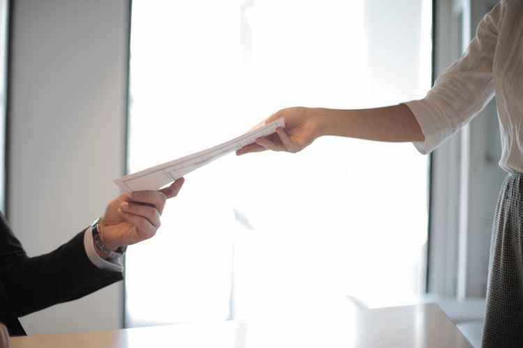 job applicant passing her documents