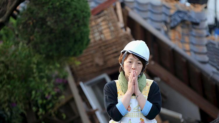 Una mujer frente a una vivienda en ruinas tras el terremoto de Mashiki, Kumamoto, Japón, 16 de abril de 2016.