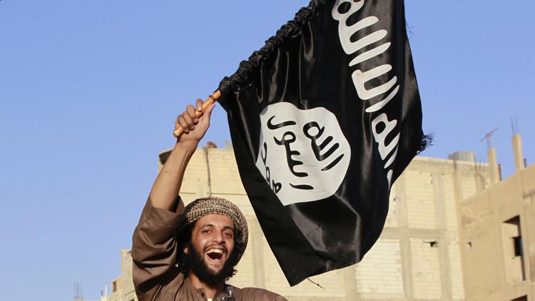 Un combatiente sostiene una bandera del Estado Islámico durante el desfile por las calles de una ciudad en la provincia de Al Raqa, al norte de Siria. 30 de junio de 2014.