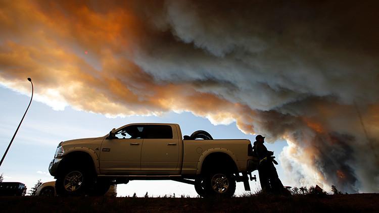 Gente esperando en un retén mientras el humo de los incendios forestales se eleva cerca de Fort McMurray, Alberta, Canadá. 6 de mayo de 2016.