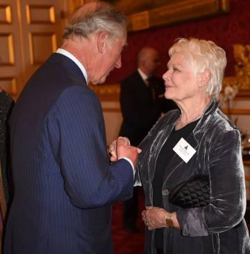 Carlos de Inglaterra conversa con la actriz Judi Dench en la recepción celebrada para los actores británicos poseedores de un Oscar..