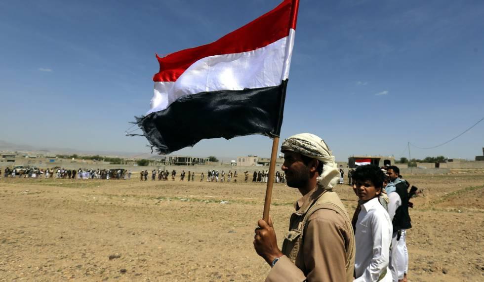Un rebelde yemení sostiene una bandera del país en los aledaños de la capita, Saná.