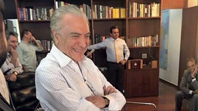 Temer, sonriendo, mirando la televisión, en su despacho del Palacio de Jaburú, con un clima de victoria
