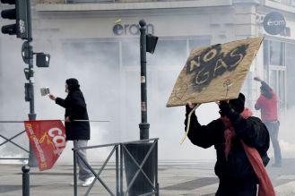 """Un manifestante sostiene un cartel que dice """"No Gas"""" en Rennes, Francia. La policía antidisturbios intenta disolver la manifestación con gases lacrimógenos. mientras los manifestantes chocan con la policía antidisturbios con gases lacrimógenos. DAMIEN MEYER (AFP)"""