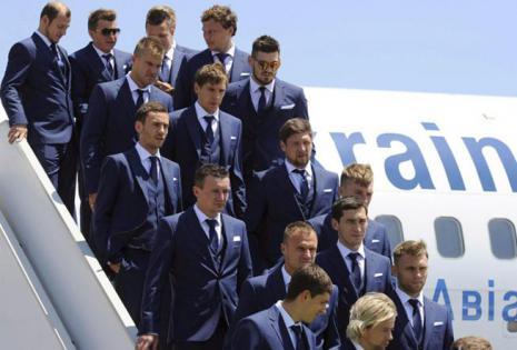 La selección de Ucrania, a su llegada al aeropuerto de Marsella, Francia. Azul marino, con chaleco y pañuelo en la solapa junto al escudo, es el traje de calle elegido por el equipo.