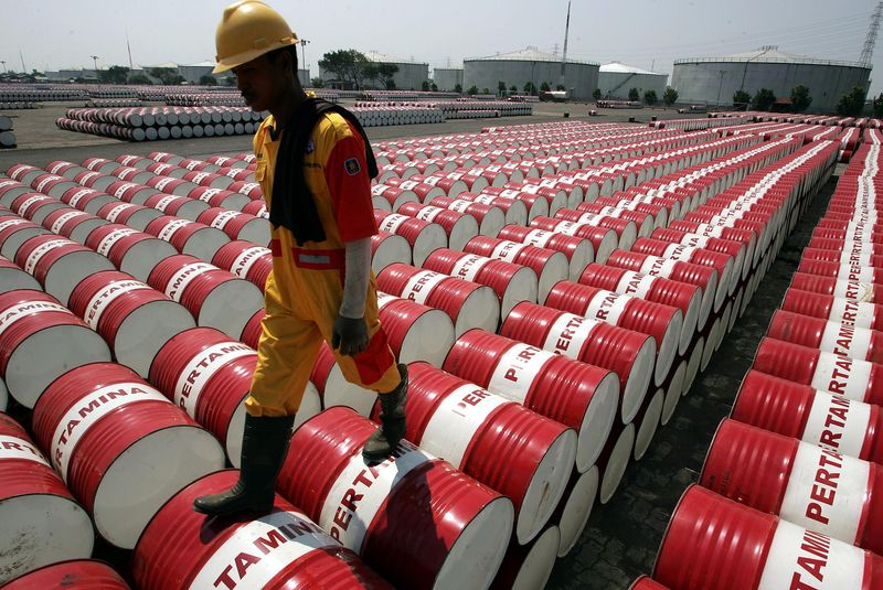 An employee of Indonesian oil company Pertamina walks on the top of drums at the oil storage depot in Jakarta in this September 1, 2005 file photo. REUTERS/Beawiharta/Files
