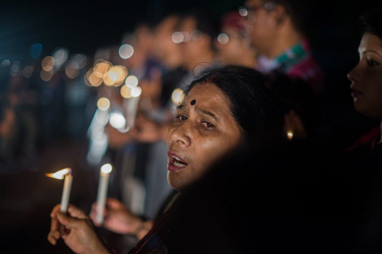"""A Bangladeshi woman sings a song for peace as she and dozens others gather in a park in for a candle-light vigil following an attack and seige in Dhaka on July 3, 2016. Bangladesh said July 3 the attackers who slaughtered 20 hostages at a restaurant were well-educated followers of a homegrown militant outfit who found extremism """"fashionable"""", denying links to the Islamic State group. As the country held services to mourn the victims of the siege in Dhaka, details emerged of how the attackers spared the lives of Muslims while herding foreigners to their deaths. / AFP PHOTO / ROBERTO SCHMIDT"""
