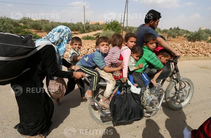 Civiles que huyeron de la violencia en la ciudad de Manbij llegan a la zona rural al sudeste de la gobernación, el 19 de junio de 2016.