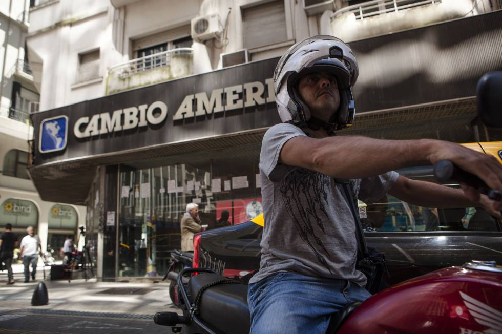 Un motociclista circula por la puerta de una de las casas de cambio más conocidas de Buenos Aires.