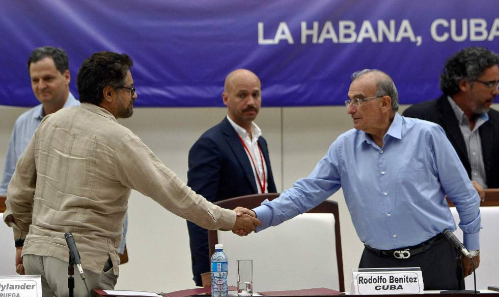 De izquierda a derecha, Iván Márquez, jefe negociados de las FARC, le da la mano a su homólogo del Gobierno, Humberto de la Calle, tras pactar los protocolos del cese al fuego.