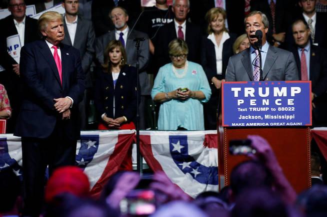 Donald Trump atiende al discurso de Nigel Farage durante un mitin en Jackson. (Reuters)