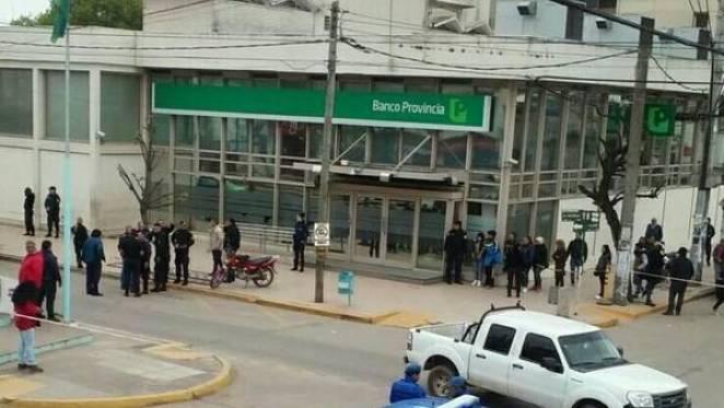 Policías y vecinos tras una salidera en el Banco Provincia de General Rodríguez. (@solorzanoRodri)