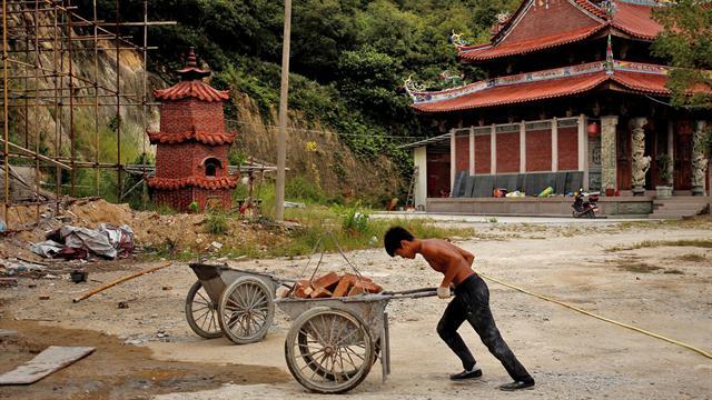 Shi Shenwei, empuja una carretilla donde se construye un templo budista en el pueblo de Huangshan, cerca de Quanzhou, provincia de Fujian, China,