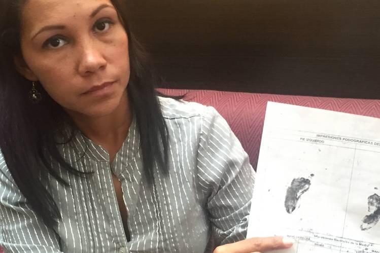 Una pariente de María de los Ángeles Carreño muestra la partida de nacimiento de Mía, una bebé prematura que murió tres horas después de nacer. La madre, de 19 años, también falleció luego de que su condición empeoró tras el parto.
