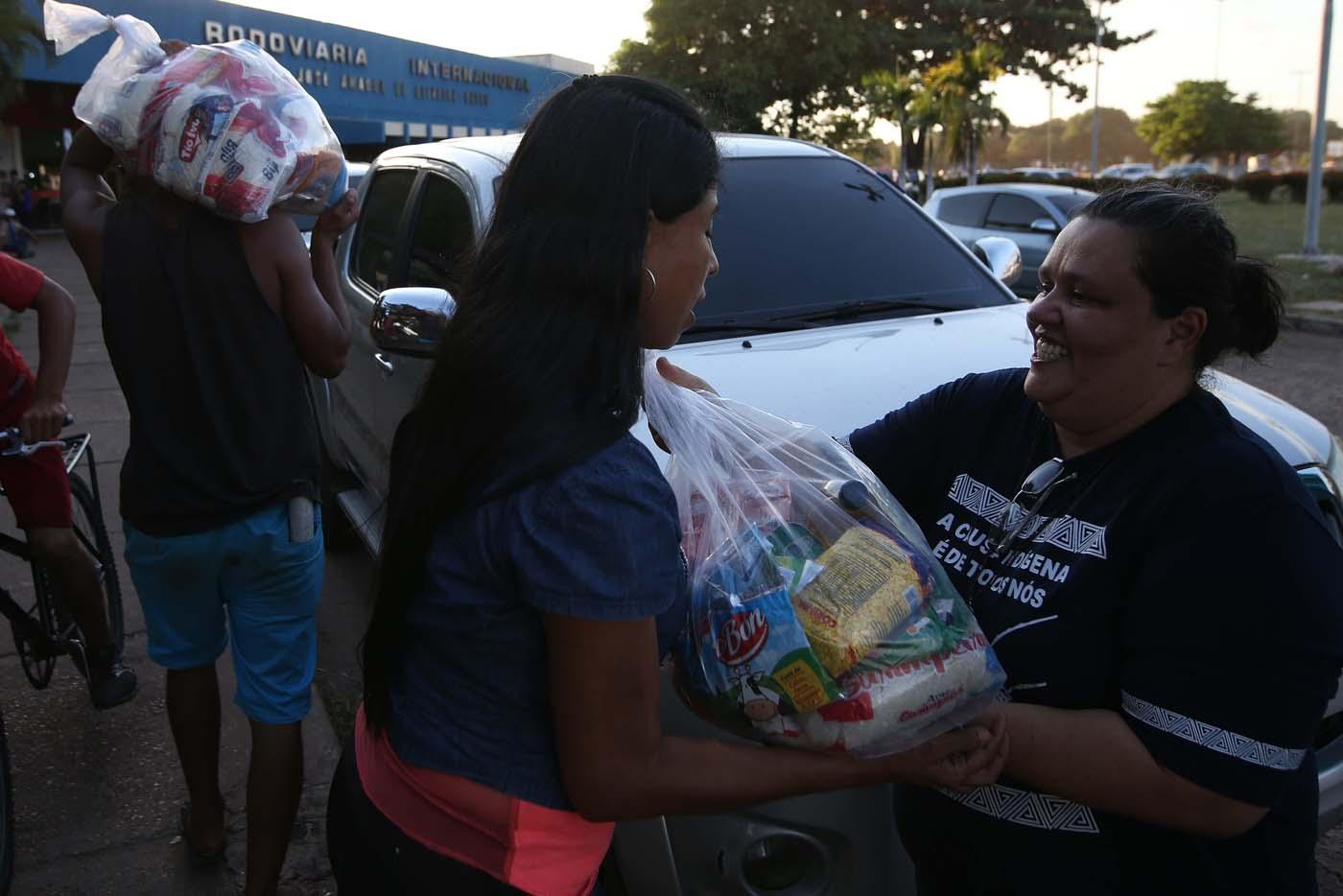 """ACOMPAÑA CRÓNICA: BRASIL VENEZUELA BRA04. BOA VISTA (BRASIL), 22/10/2016.- La coordinadora de la Comisión de Migración y Derechos Humanos del estado brasileño de Roraima, Telma Lage, entrega alimentos a inmigrantes venezolanos este jueves, 20 de octubre de 2016, en Boa Vista, estado de Roraima (Brasil). Es venezolana, tiene 20 años, quiere ser traductora y hoy, en una hamaca colgada en un árbol que ha convertido en su casa en la ciudad brasileña de Boa Vista, mece unos sueños que, según aseguró, no serán truncados por """"el fracaso de una revolución"""". """"No estoy aquí por política. Lo que me trajo aquí fue el fracaso de unas políticas"""", dijo a Efe Sairelis Ríos, quien junto a su madre Keila y una decena de venezolanos vive en plena calle, frente a la terminal de autobuses de Boa Vista, una ciudad que en los últimos meses ha recibido unos 2.500 emigrantes de ese país vecino. EFE/Marcelo Sayão"""