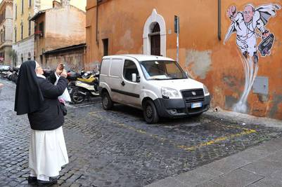 Una monja toma una foto del mural del Papa Francisco, realizado por Maupal, poco antes de ser borrado. / AFP