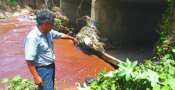 El vecino Raymundo Ríos muestra cómo el agua pasa por debajo de la alcantarilla, socavando la estructura, que se puede venir abajo