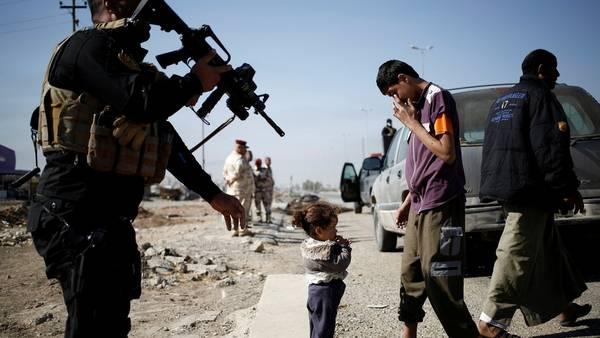 Salida. Una nena que fue rescatada desde un barrio al este de Mosul espera en un puesto de control de las fuerzas iraquíes en la cercana localidad de Kokjali, este sábado. /REUTERS