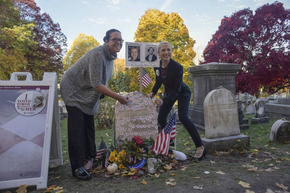 Lisa Walden, a la izquierda, y Steph Kula, de Rochester, colocan pegatinas con el eslógan 'Yo voté', en la tumba de Susan B. Anthony, en el día de las elecciones estadounidenses, en el cementerio Mount Hope de Rochester, Nueva York (EE UU).