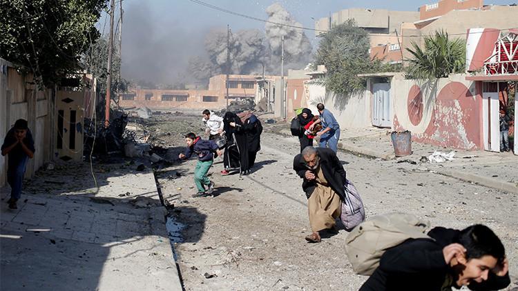 Vecinos de Mosul (Irak) corren despavoridos en medio de un ataque aéreo de la coalición contra posiciones del Estado Islámico en el barrio de Tahrir, el 17 de noviembre de 2016.