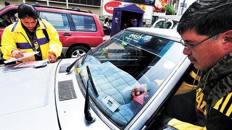 Un funcionario de una aseguradora coloca el sticker del SOAT en un auto de transporte público