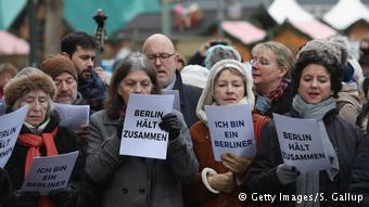 Refugiados y alemanes cantan en honor a las víctimas del atentado en Berlín.
