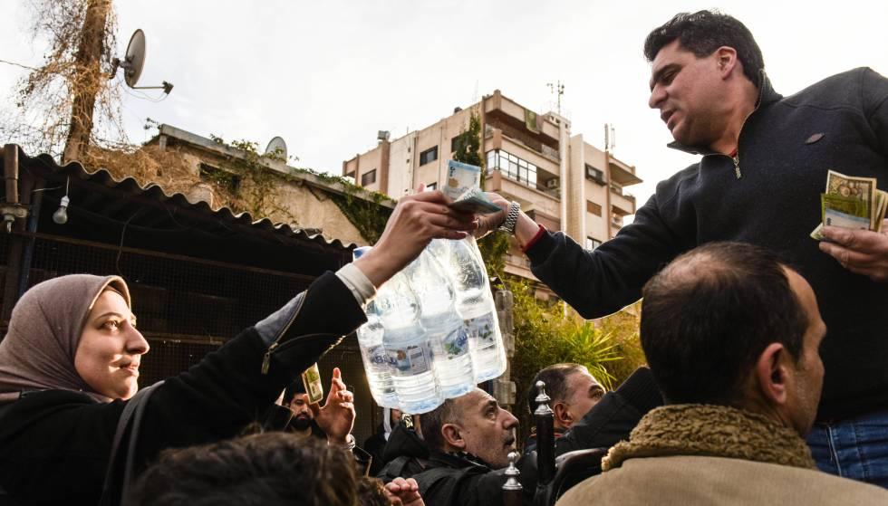 Un hombre vende botellas de agua mineral en un barrio de Damasco.