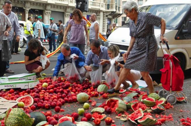 Asociación Agraria de Jóvenes Agricultores (Asaja), repartiendo productos frente al consulado de Francia como protesta. (EFE)