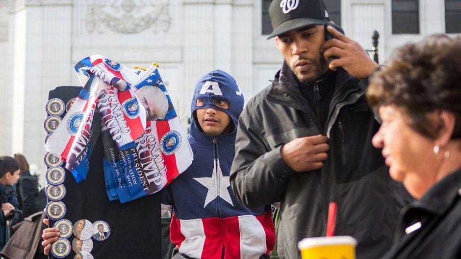 Un hombre vestido como Capitán América vende botones y banderas de Trump para su llegada a la Casa Blanca. (Crédito: Jessica Kourkounis/Getty Images)