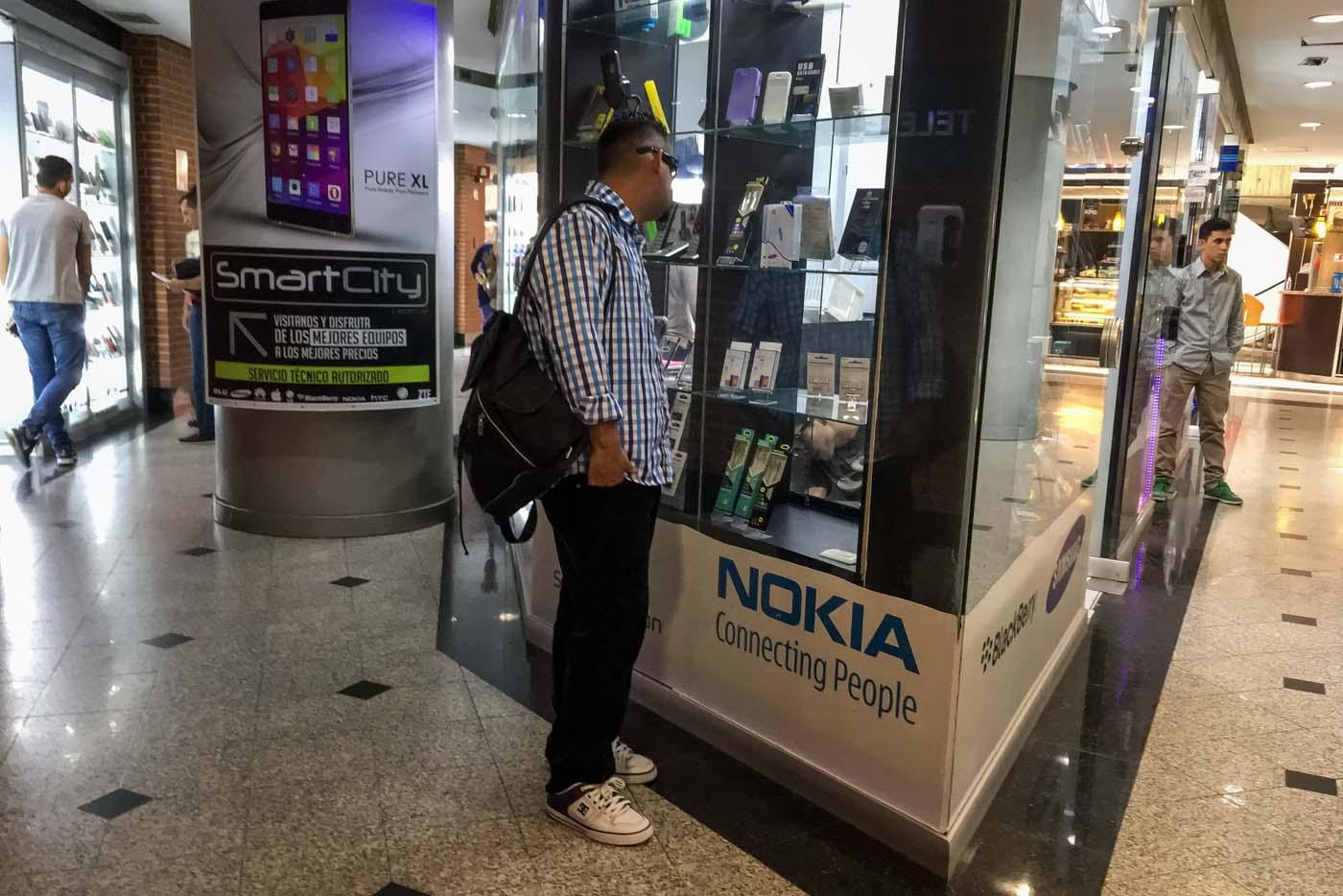 ACOMPAÑA CRÓNICA: VENEZUELA DIVISAS - CAR01. CARACAS (VENEZUELA), 27/01/2017.- Fotografía del 25 de febrero del 2017, donde se observa a una persona ver una vitrina en un centro comercial en la ciudad de Caracas (Venezuela). En una vitrina de una tienda caraqueña se exhibe un móvil de última generación a un precio de 1.280.000 bolívares, una cantidad que puede pagarse con dólares estadounidenses en este lugar y en otros que operan con varias divisas pese al control de cambio que rige en Venezuela desde 2003. EFE/MIGUEL GUTIÉRREZ