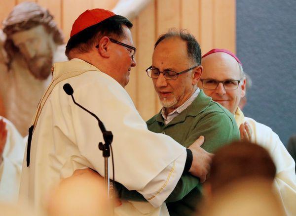 El cardenal Gerald Cyprien Lacroixabraza al cofundador del Centro Cultural Islámico de Quebec,Boufeldja Benabdallah, durante una misa en Quebec City este martes (Reuters)