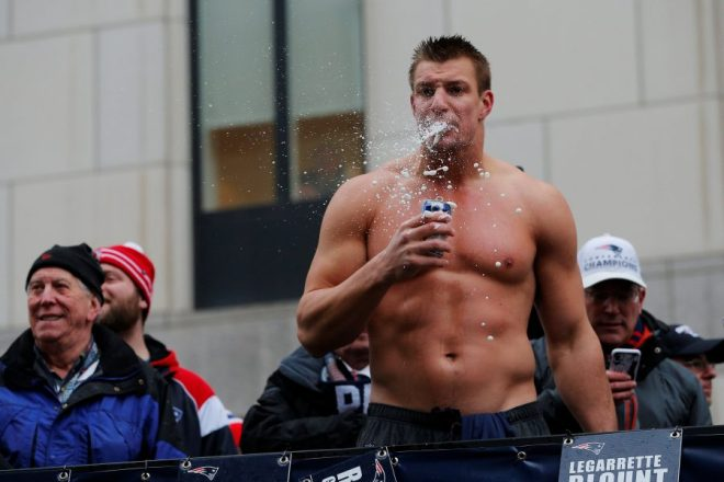 New England Patriots tight end Rob Gronkowski drinks a beer thrown to him from the crowd during the Patriots victory parade through the streets of Boston after winning Super Bowl LI, in Boston