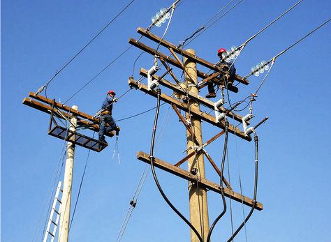 Obreros realizan trabajos en un poste de electricidad. Foto: ENDE