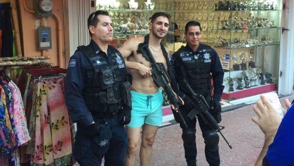 Dos policías federales acceden a tomarse fotos con un turista, mientras que uno de ellos le permite posar con su rifle de asalto reglamentario, aparentemente descargado